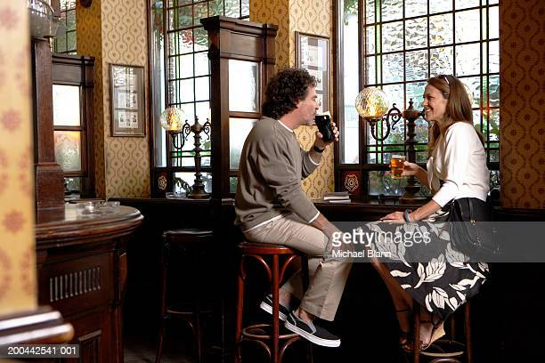 Mature couple sitting on bar stools having drinks in pub, smiling