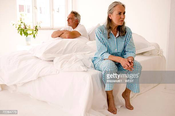 mature couple sitting on bed (focus on woman in foreground) - northern european descent stock pictures, royalty-free photos & images
