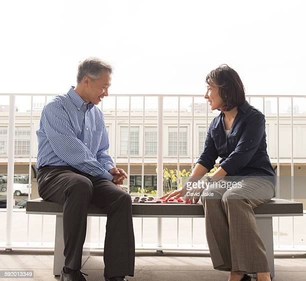 Mature couple sitting on bench face to face playing draughts