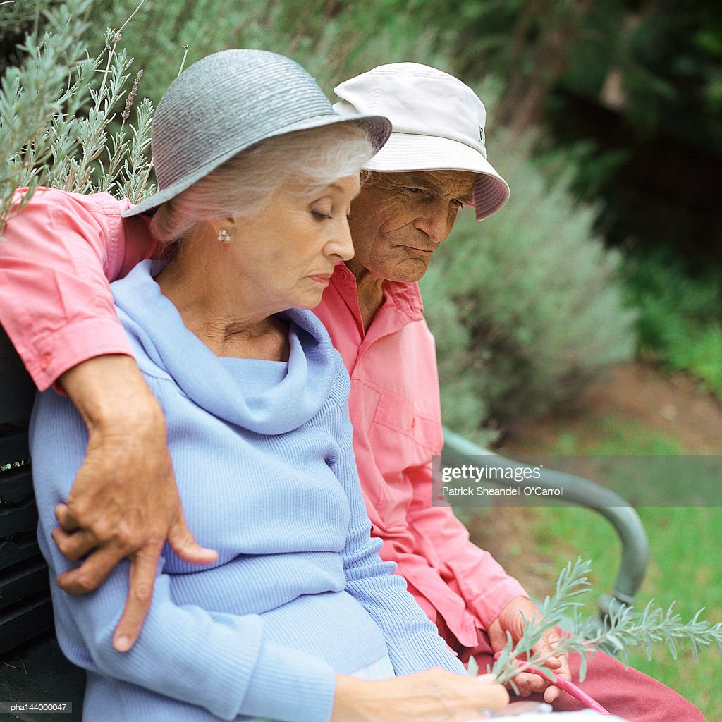Mature couple sitting on bench outside : Stockfoto