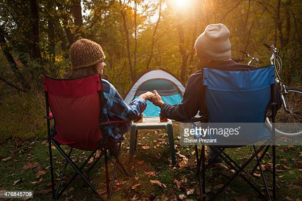 Mature couple sitting on camping chairs outside tent, holding hands