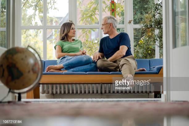 mature couple sitting on couch at home talking - einfaches leben stock-fotos und bilder