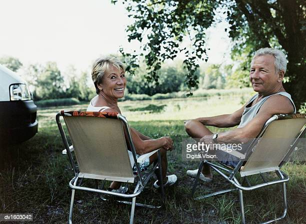 Mature Couple Sitting on Deckchairs by a Lake, Looking Back at the Camera