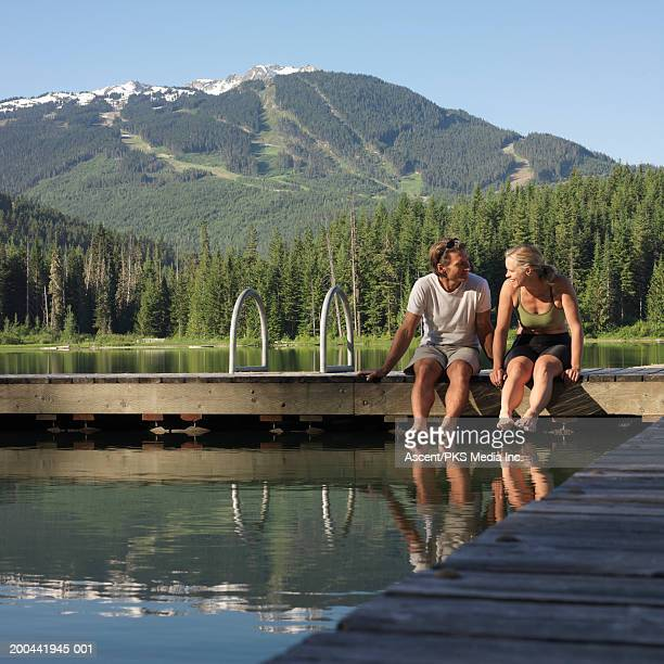 mature couple sitting on dock at lake, sunrise - close to stock pictures, royalty-free photos & images