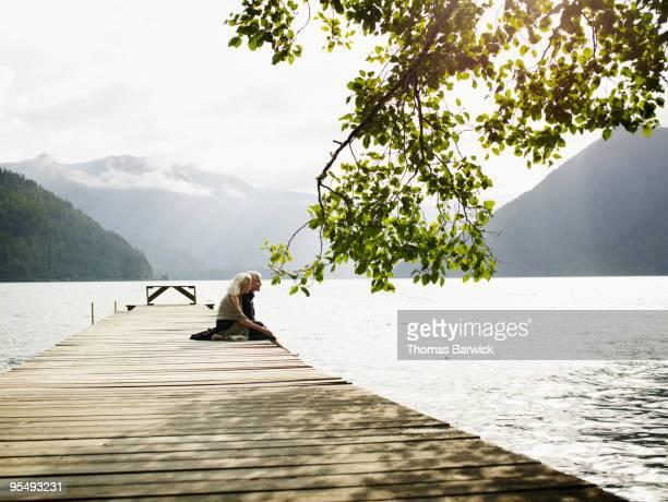 mature couple sitting on edge of dock on lake - ponton photos et images de collection