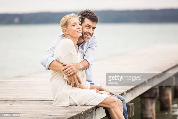Mature couple sitting on edge of pier, hugging