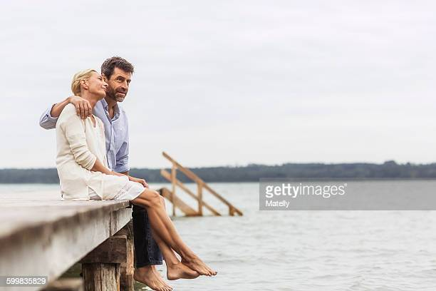 Mature couple sitting on edge of pier, relaxing