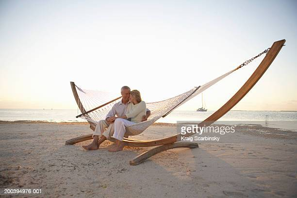 Mature couple sitting on hammock on beach, heads together