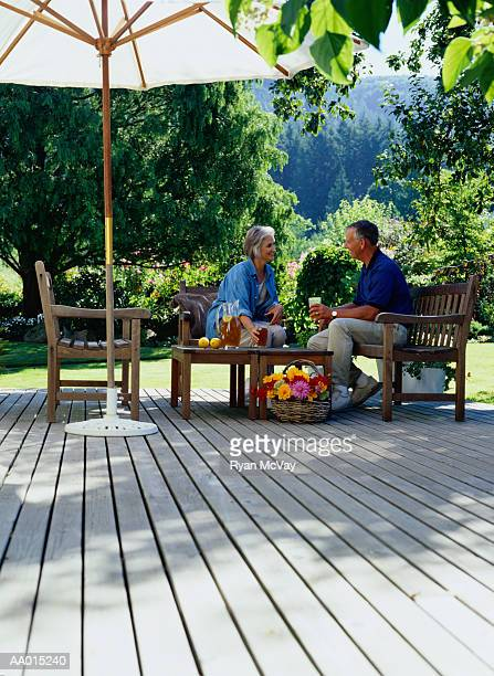 Mature couple sitting on outdoor deck drinking iced tea