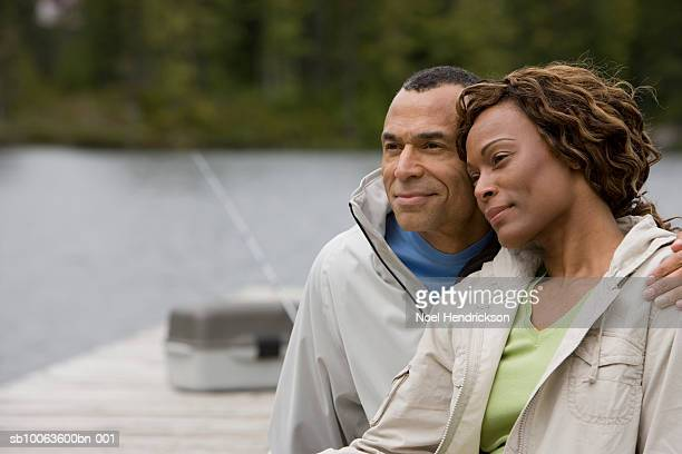 Mature couple sitting on pier embracing