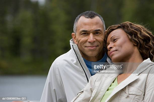Mature couple sitting on pier, man looking at camera