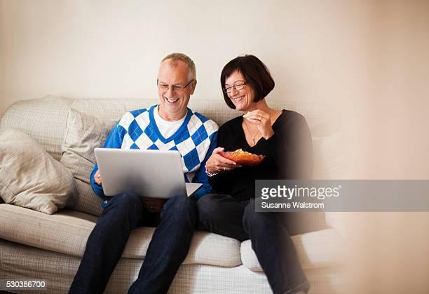 Mature couple sitting on sofa watching laptop