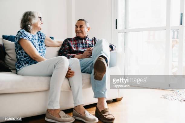 volwassen paar zittend op de bank samen thuis - 65 69 jaar stockfoto's en -beelden