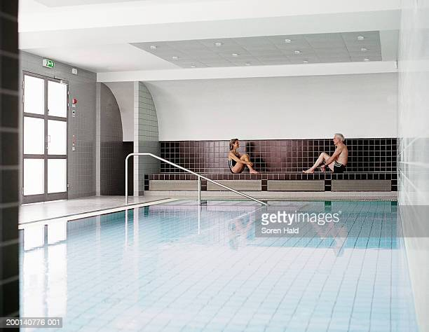 Mature couple sitting on tiled bench by indoor swimming pool