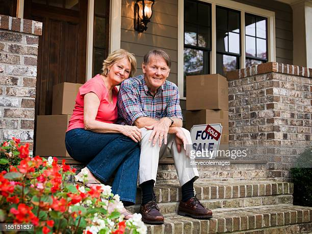 mature couple sitting outside house with for sale sign - vendor stock pictures, royalty-free photos & images