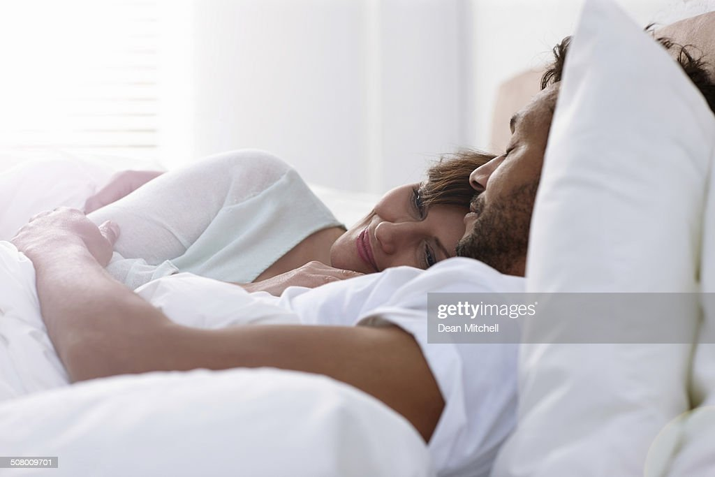 Mature couple sleeping in bed together : Stock Photo