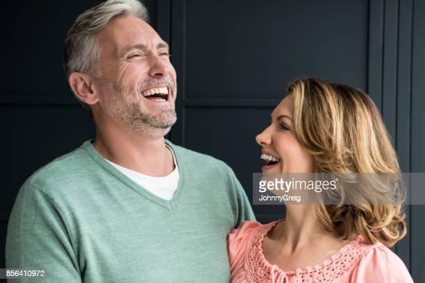 Couple senior souriant et riant devant les panneaux bleu foncé