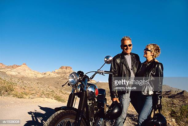 Mature Couple Smiling and Standing Next to a Motorbike in the Desert