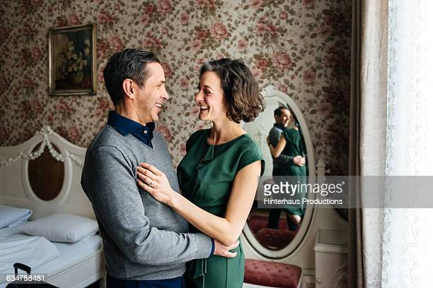 Mature couple smiling in a hotel room.