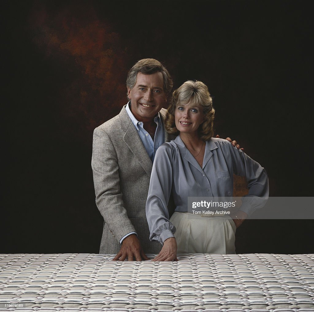 mature couple standing against black background smiling portrait