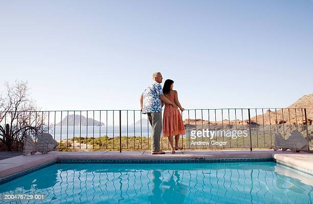Mature couple standing against railing of balcony, pool in foreground
