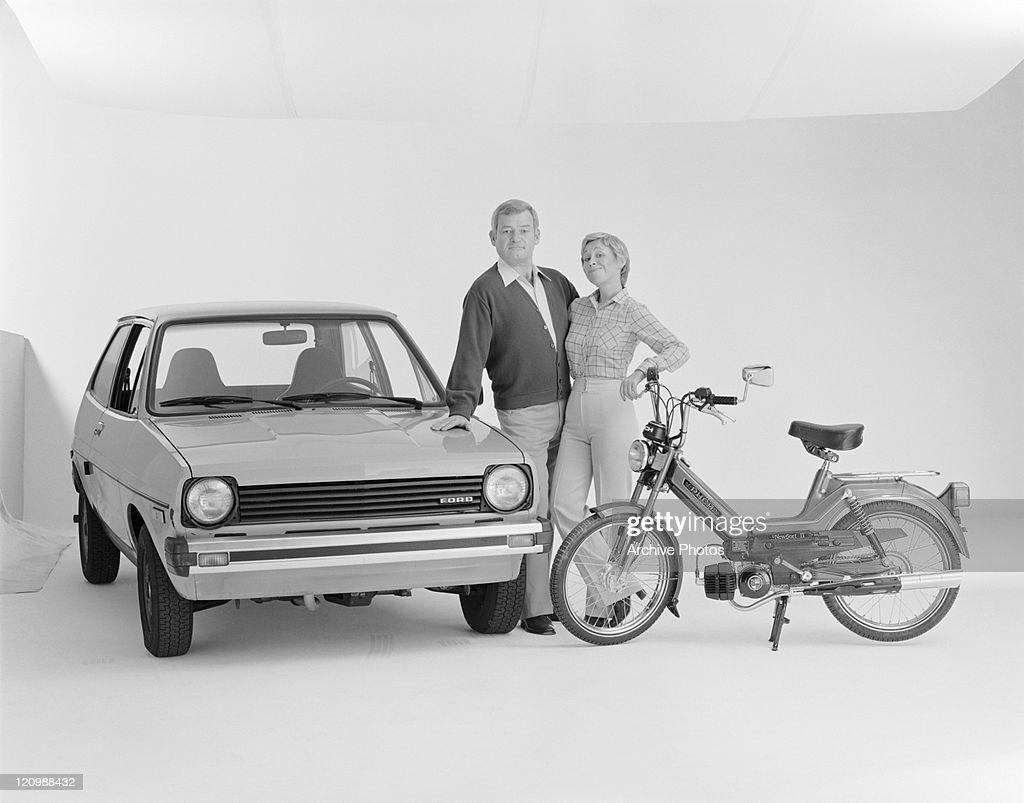 mature couple standing beside ford fiesta and puch moped smiling