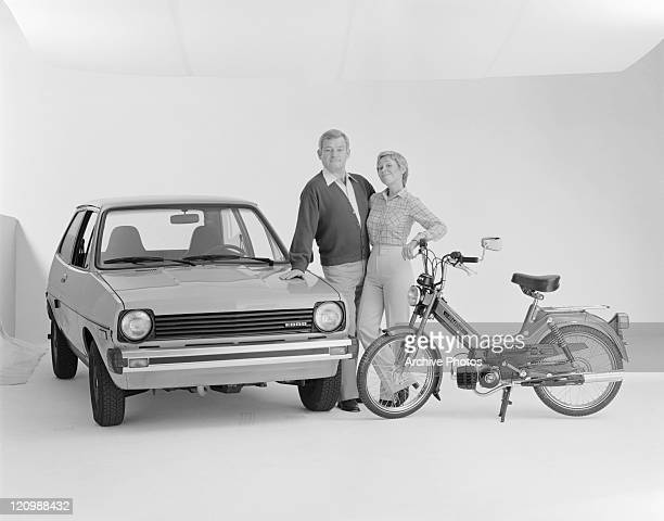 Mature couple standing beside Ford Fiesta and Puch moped, smiling, portrait