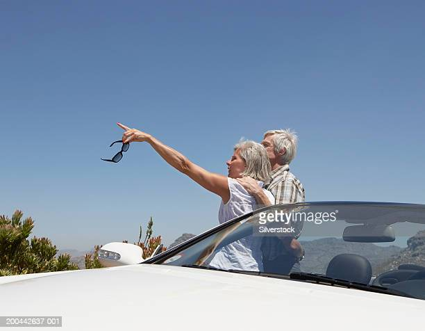 mature couple standing by convertible car, woman pointing - next to stock pictures, royalty-free photos & images