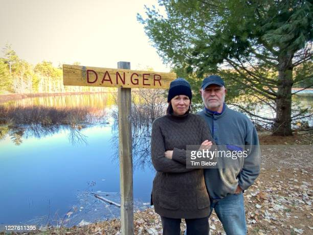 mature couple standing by danger sign on hike in woods - deadly exchange stock pictures, royalty-free photos & images