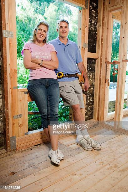Mature couple standing in construction frame, portrait