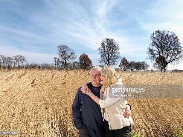 mature couple standing in field - colin hawkins stock pictures, royalty-free photos & images