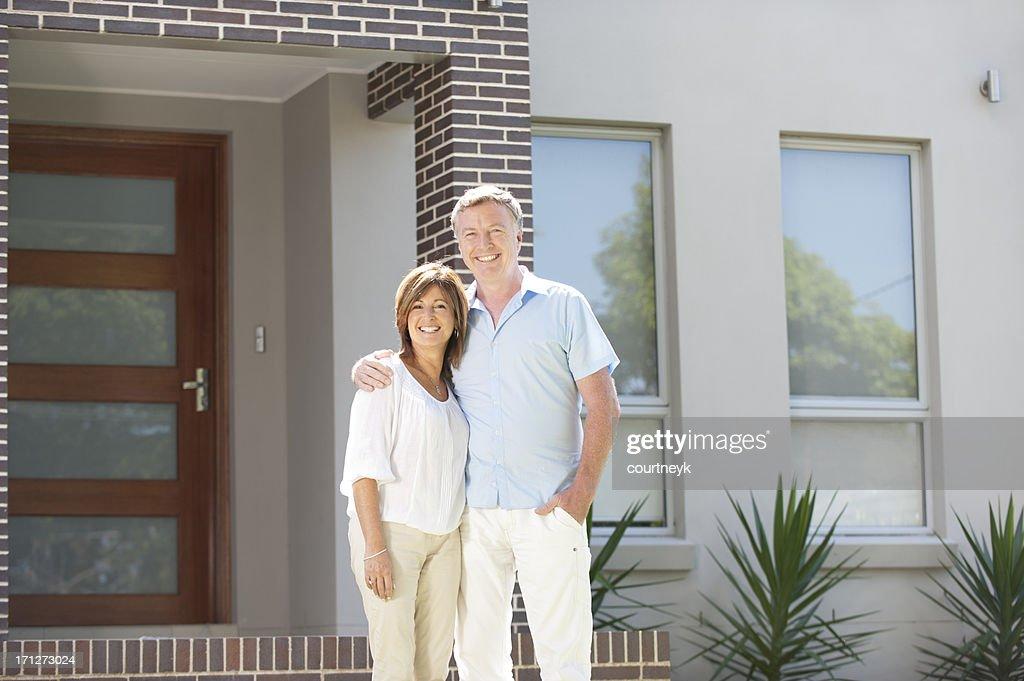 Casal em pé na frente de uma casa Moderna : Foto de stock