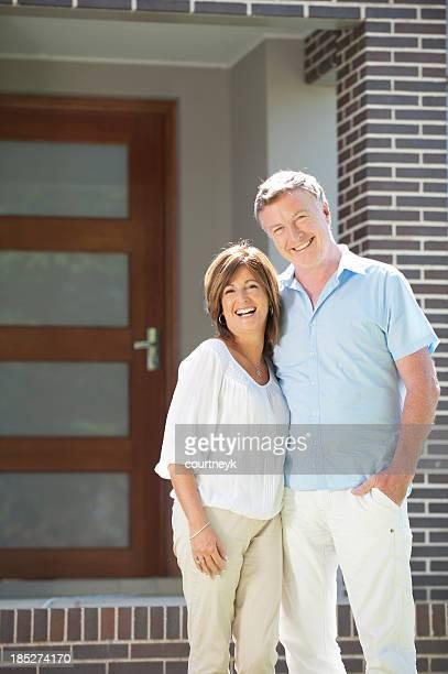 Älteres Paar stehen vor einem modernen Haus