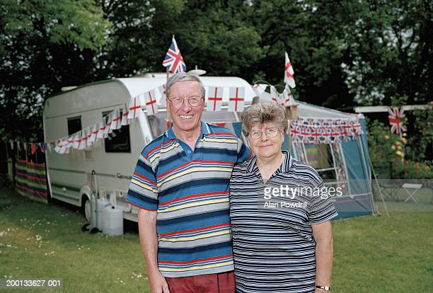 Mature couple standing in front of caravan, portrait