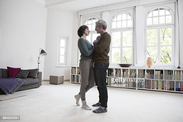 Mature couple standing in living room