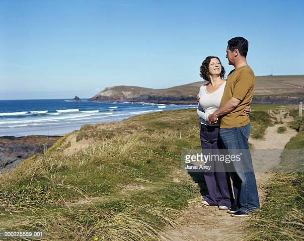 Mature couple standing on path by sea, smiling