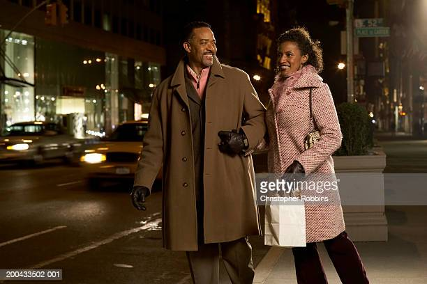 Mature couple standing on pavement holding hands, smiling, night