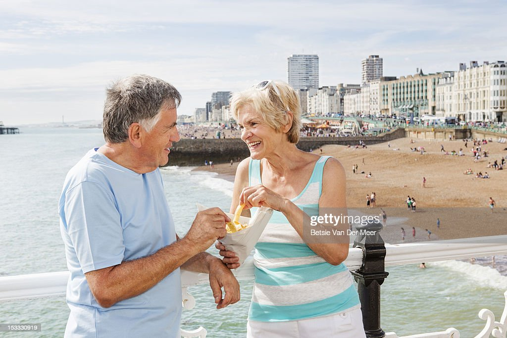 Mature couple standing on pier eating chips. : Stock-Foto
