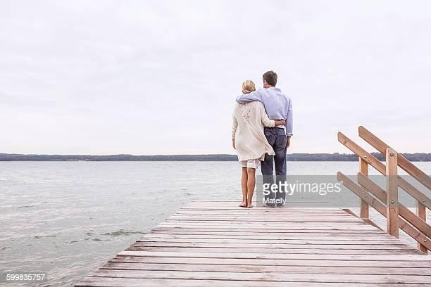 mature couple standing on pier, looking at view, rear view - passer le bras autour photos et images de collection