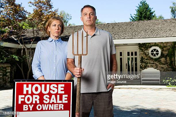 Mature couple standing outside newly bought property in style of American Gothic