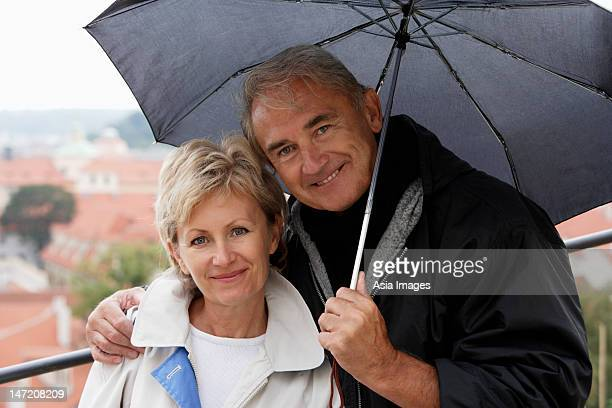mature couple standing under an umbrella and smiling
