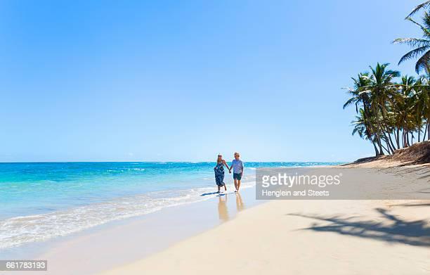 Mature couple strolling along beach, Dominican Republic, The Caribbean
