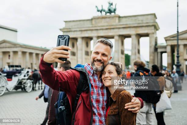 a mature couple take a selfie together in front of brandenburg gate in berlin - toerist stockfoto's en -beelden