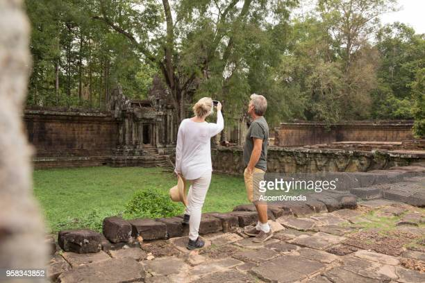 mature couple take photo of temples and jungle, angkor wat - ancient civilization stock photos and pictures