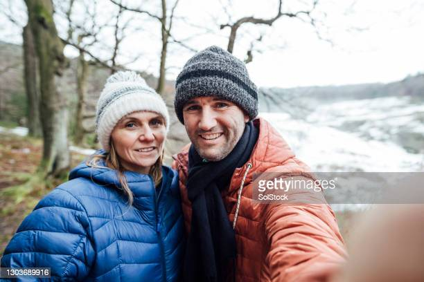 mature couple taking a selfie together in the woods - coat stock pictures, royalty-free photos & images