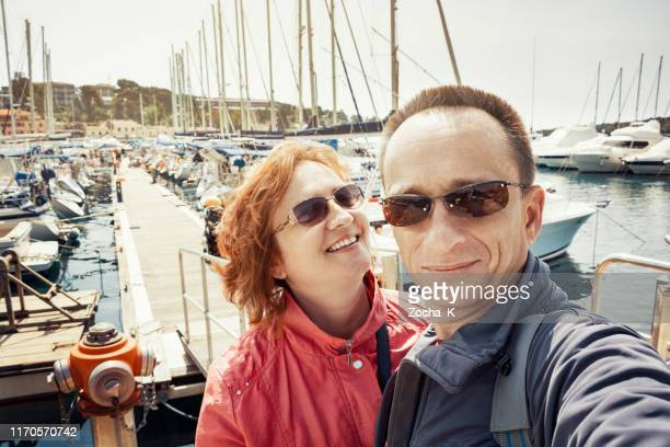 mature couple taking selfie in front of a marina - mid adult stock pictures, royalty-free photos & images