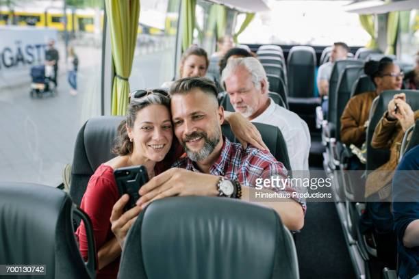 A Mature Couple Taking Selfie On Bus