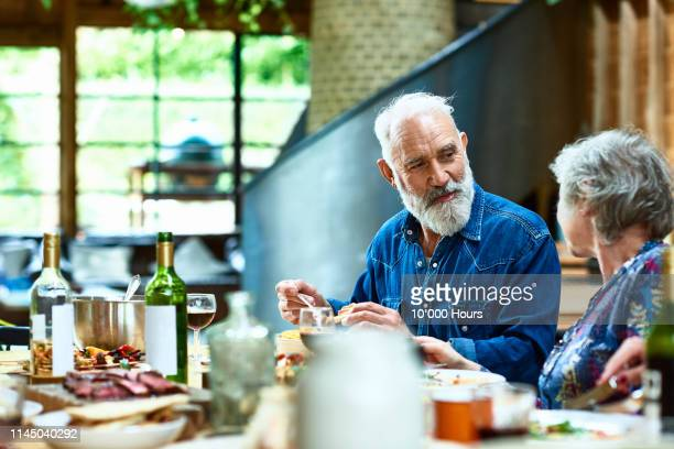 mature couple talking at dinner table with food and wine - drink stock pictures, royalty-free photos & images