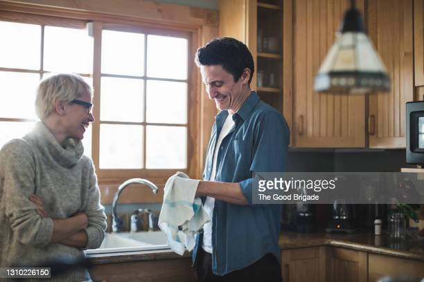 mature couple talking in kitchen at home - housework stock pictures, royalty-free photos & images