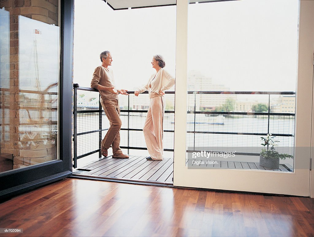 Mature Couple Talking on the Balcony of Their Apartment : Stock Photo